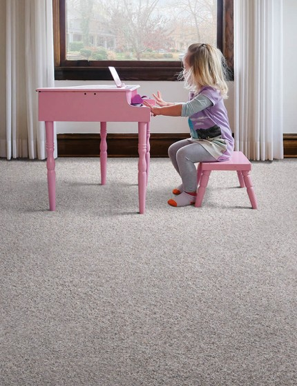 Girl with piano on grey carpet | We'll Floor You