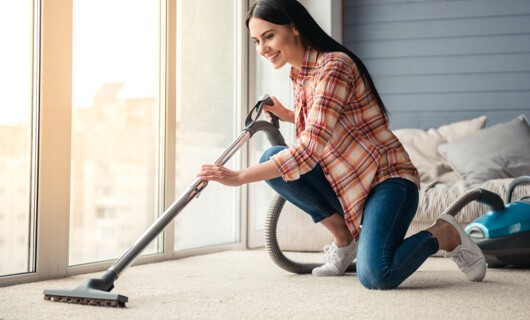 Lady vaccuming carpet | We'll Floor You